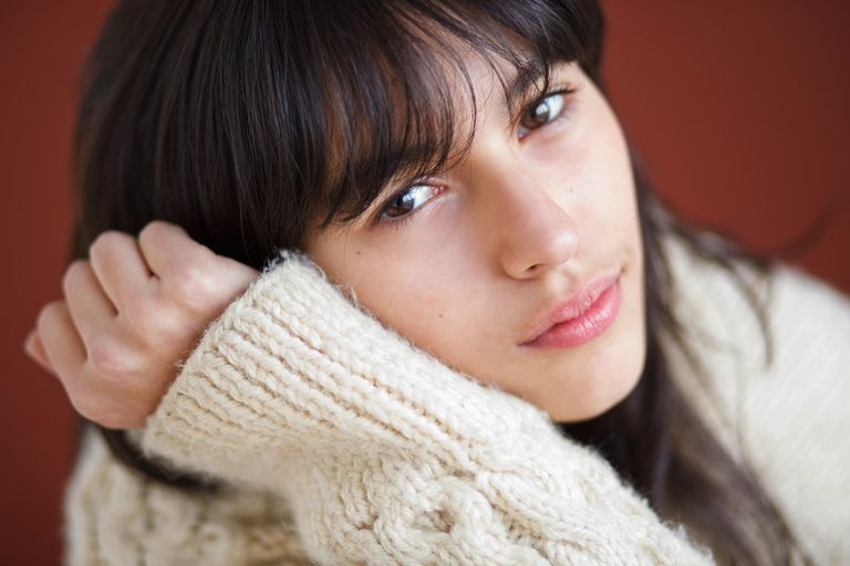 Teenage girl in a sweater looking like she doesn't feel well.