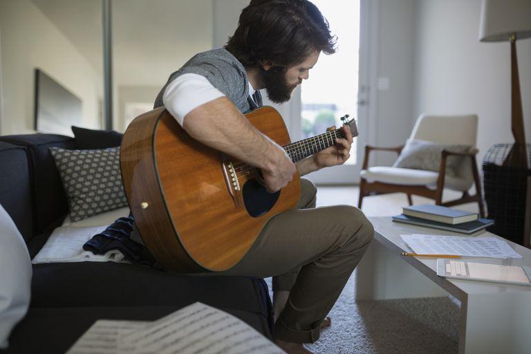 Man playing guitar writing music in living room