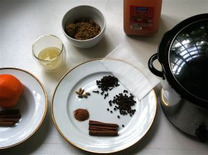 An image of apple cider, cardamom, allspice, cloves, cinnamon, nutmeg, brown sugar and an orange.