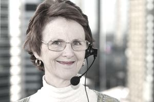 Smiling mature woman in an office wearing a headset.