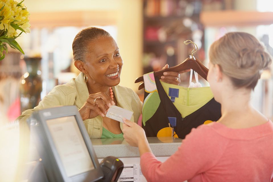 Woman purchasing clothing with credit card in store.