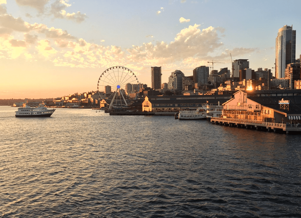 cruise ship sailing into pier 55 in seattle at sunset with a backdrop of the ferris wheel and city