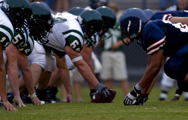 American Football Players at Line of Scrimmage during Football Game