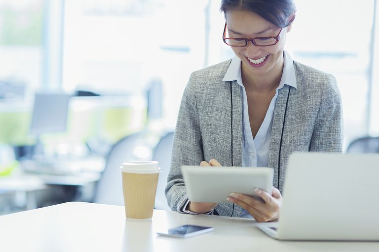 Smiling businesswoman on tablet