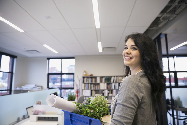 Woman carries her office things to he new internal job because she responded to her employer's job posting.