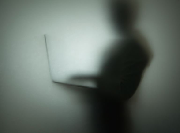 Photo of a silhouette of person using laptop behind glass