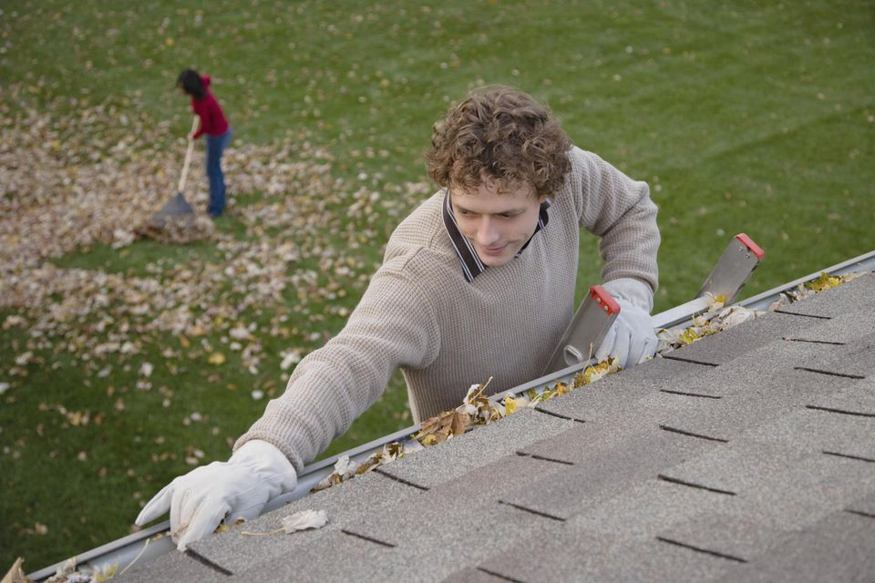 Man cleaning leaves out of gutter