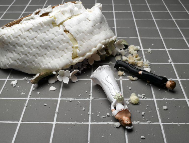 Torta de matrimonio y figuras de novios en el suelo.