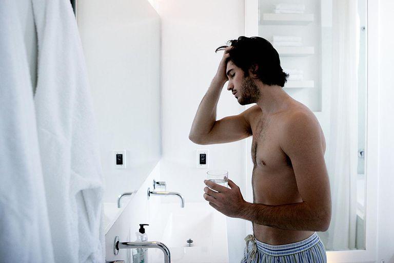 Man rubbing head in bathroom