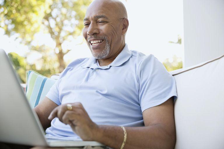 Happy senior man using laptop on outdoor sofa
