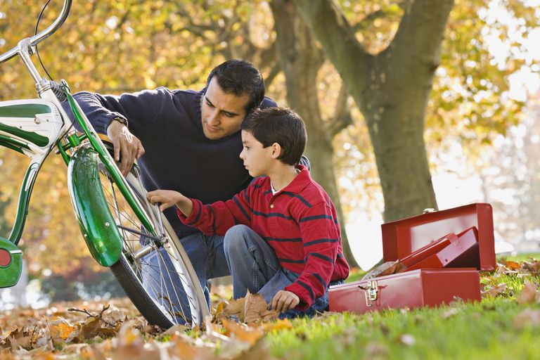 Hispanic father and son fixing bicycle