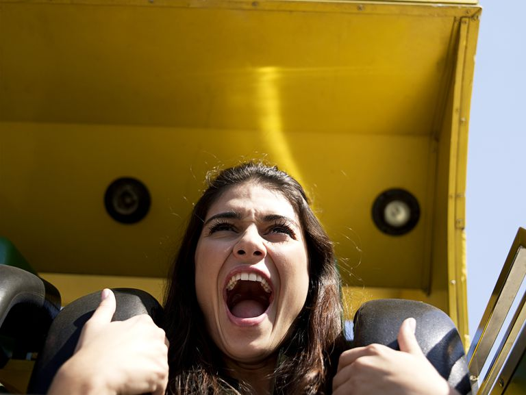 Young woman enjoying amusement park ride, close-up