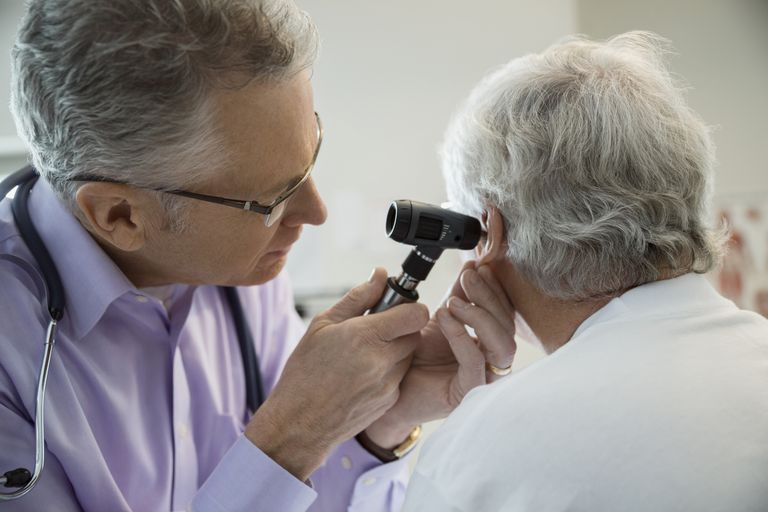 Doctor checking senior mans ears with otoscope