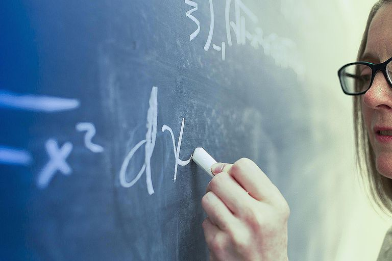 A woman writes path analysis equations on a chalk board.
