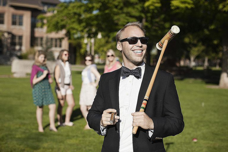 A smiling white man holds a cigar and croquet mallet on the lawn of a luxurious estate, demonstrating how cultural capital can be demonstrated.