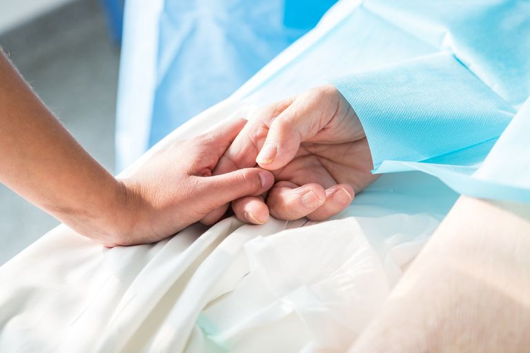 Closeup of woman holding a patient's hand
