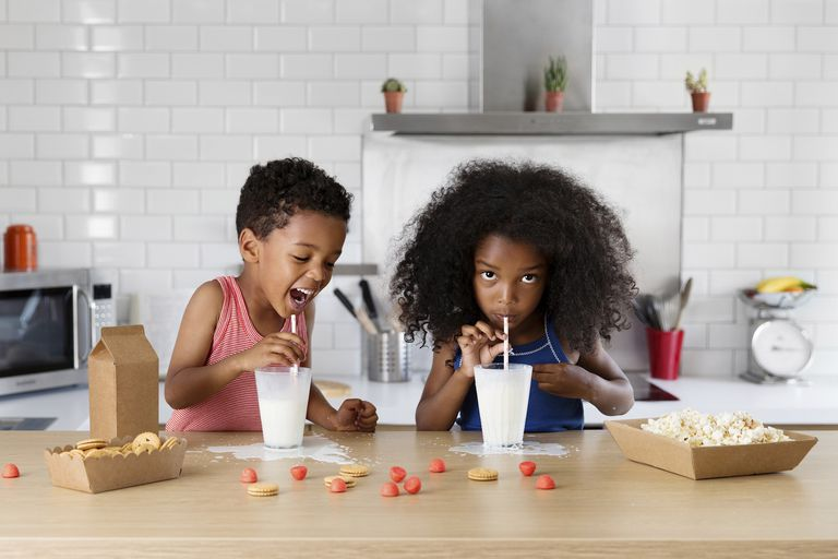 Brother and sister drinking milk in the kitchen