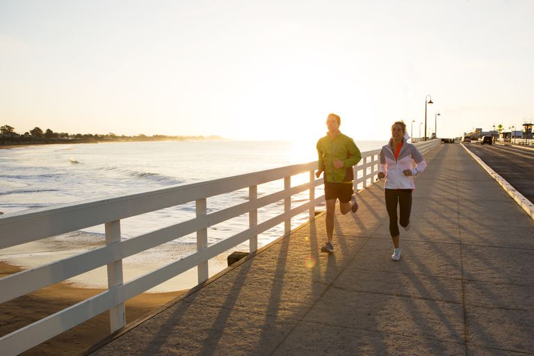 Couple running by the water at sunset
