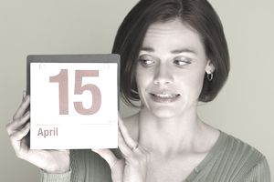 woman holding up a calendar with the date April 15