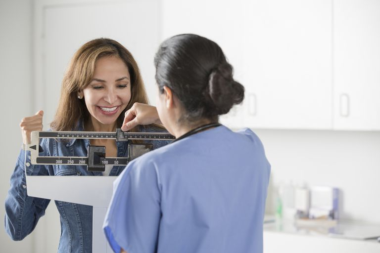 smiling woman being weighed by doctor