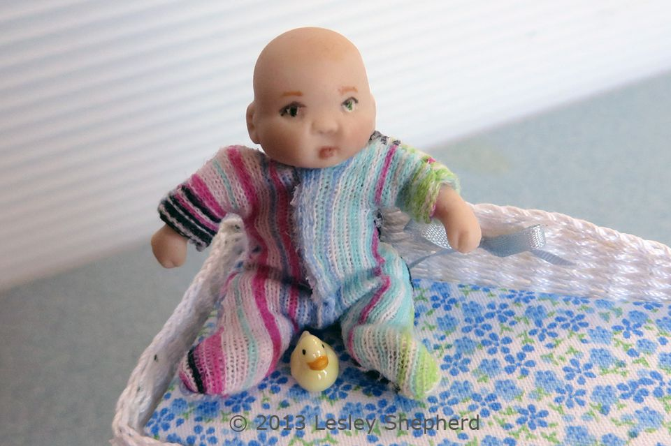 Dollhouse baby doll in a custom fitted stretch baby sleeper with a velcro closure.
