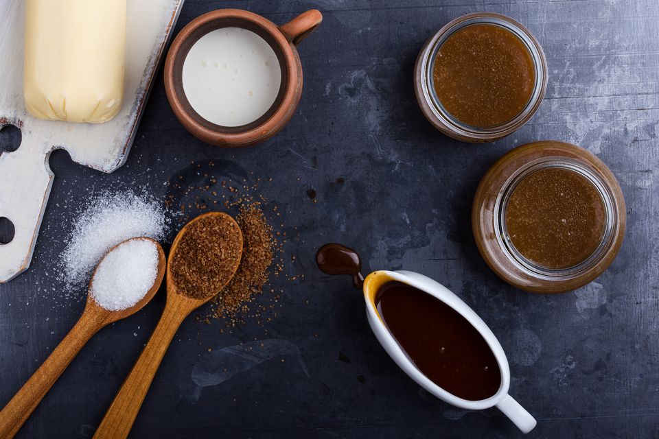 Homemade caramel sauce in glass jars and ingredients
