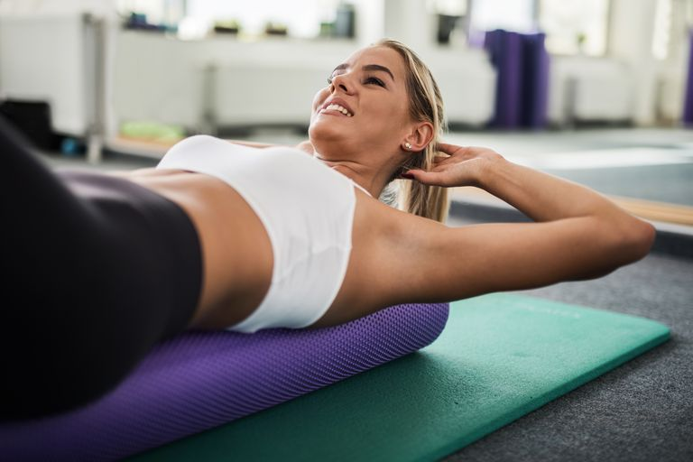 Young female athlete exercising in a health club.