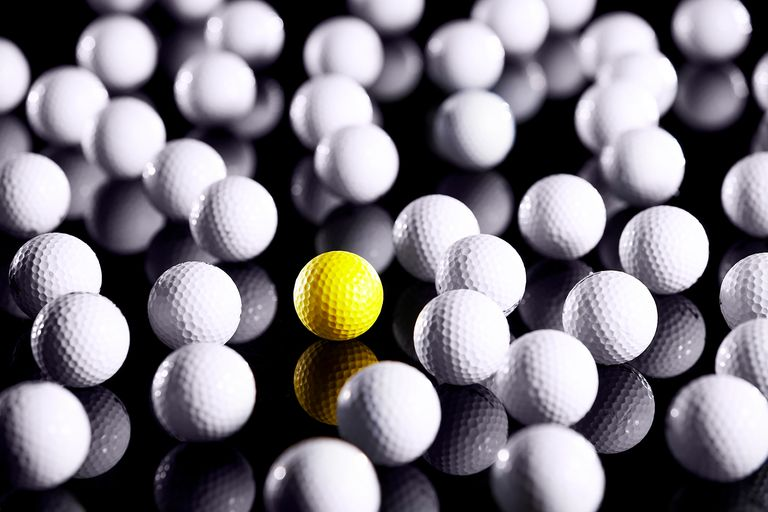 White golf balls with one yellow one.
