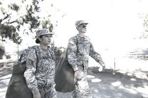Army woman and man walking with duffelss
