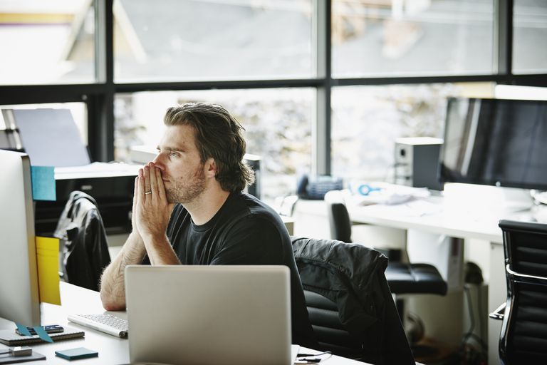Man in office working on two workstations