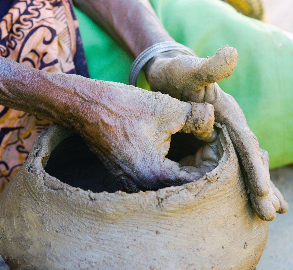 Elderly female potter making a clay pot