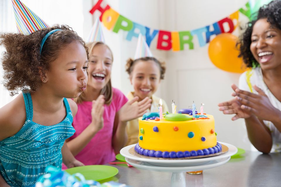 Child blowing out candles on a birthday cake