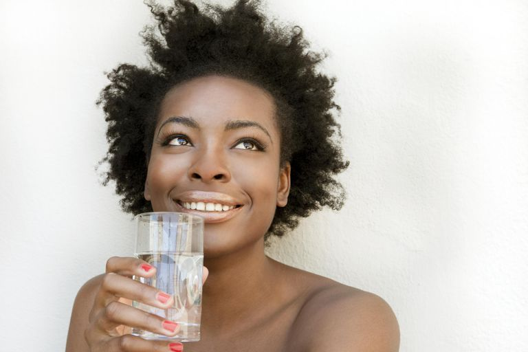 Woman drinking water, a great ingredient to keep black hair healthy