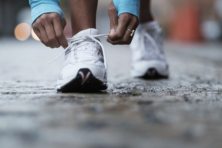 Black woman tying her running shoe
