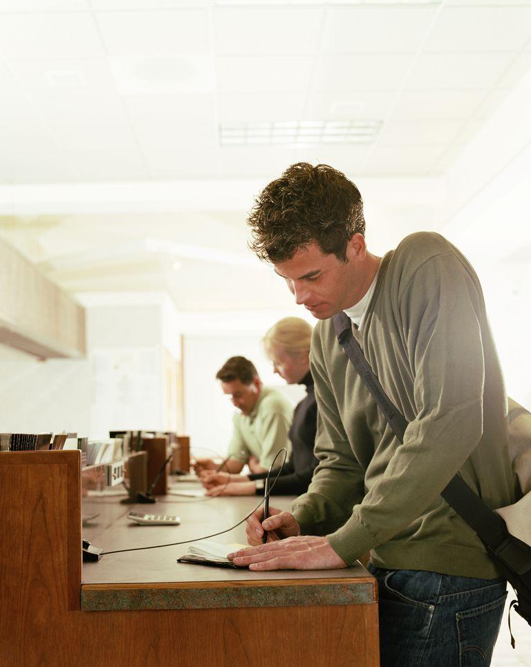 Young man writing check on counter of bank
