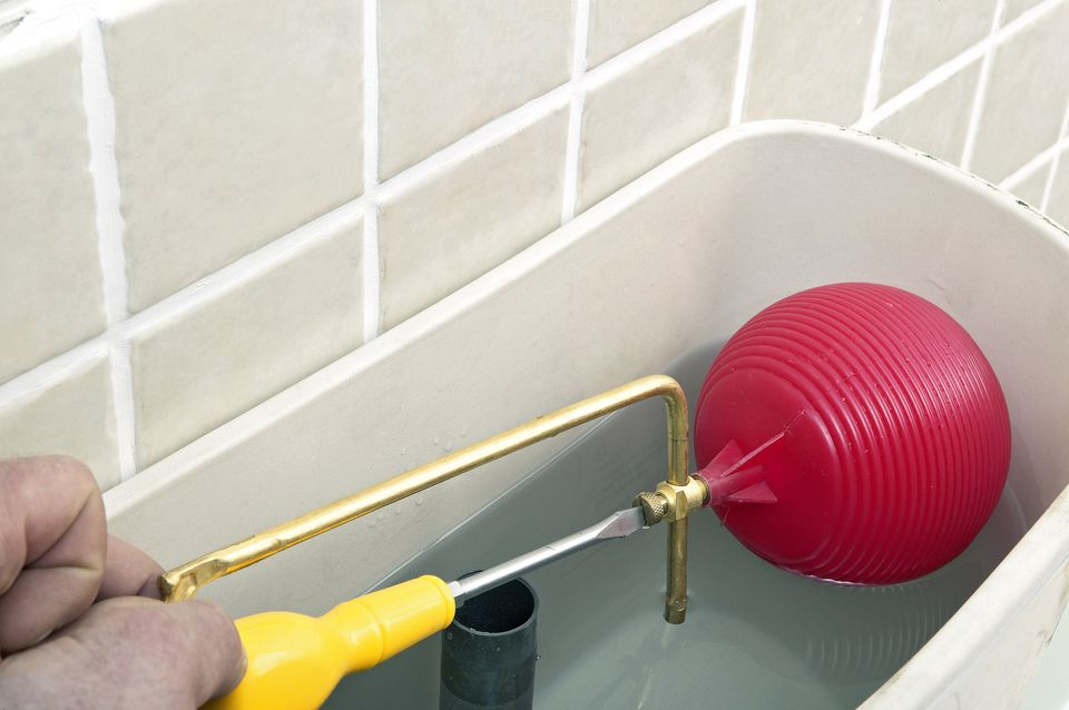Man using screwdriver to adjust screw on float arm in toilet cistern