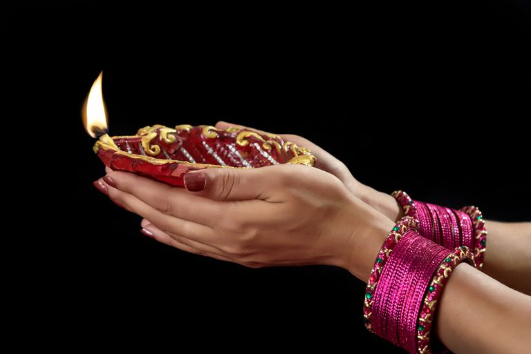 Woman with lit earthen lamp at Diwali festival.