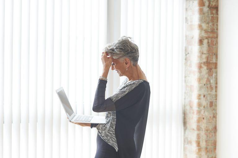 Stressed older woman using laptop