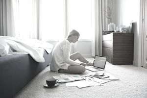 Woman paying bills at laptop on bedroom floor