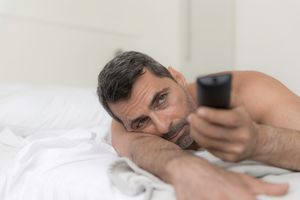 Bare shouldered mature man lying on front on bed using remote control