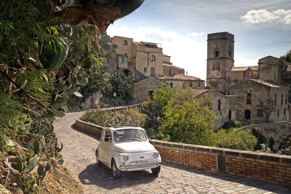 Classic Fiat 500 driving in the village of Savoca Sicily