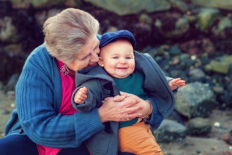 Grandmother holding her baby grandson on a beach in Washington State