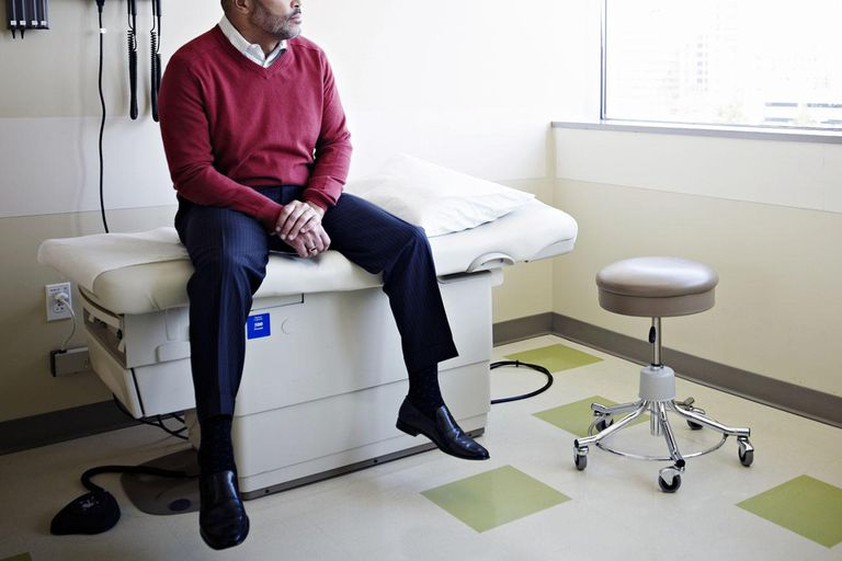 Mature male patient sitting on exam table looking out window in clinic room