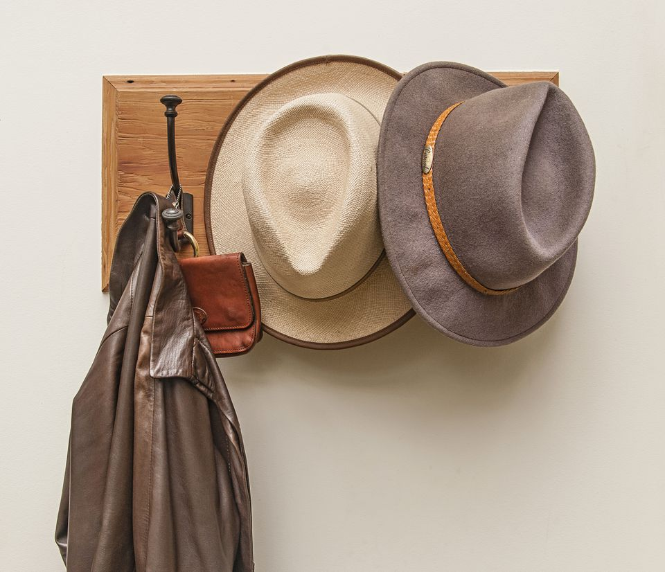 Wooden hat rack with 2 hats, leather bag and leather jacket. Still life.