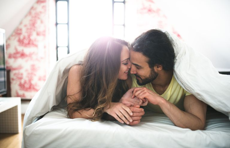 couple kissing on the bed in the early morning