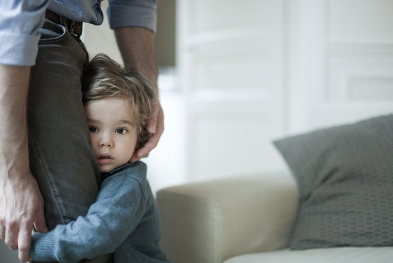 shy toddler boy holding into dad's legs