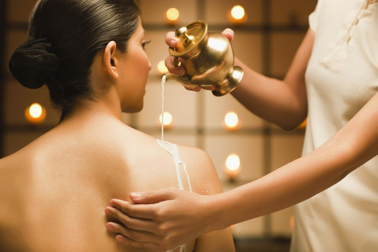 Massage therapist pouring oil over young woman's back in preparation for massage
