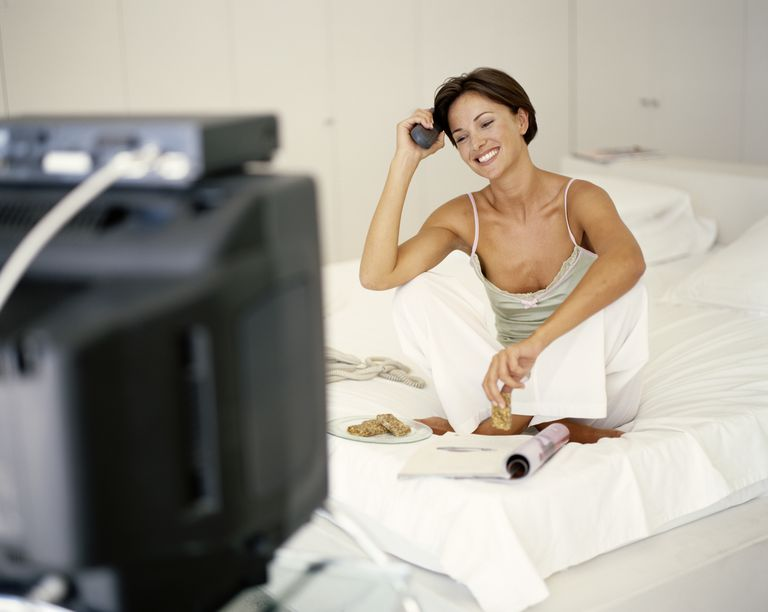 Woman sitting on bed, watching television smiling(focus on woman)
