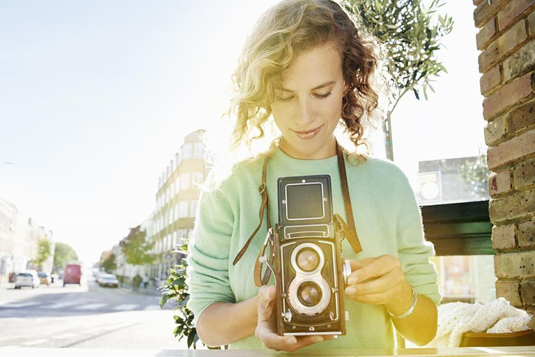 Woman taking photograph with vintage camera