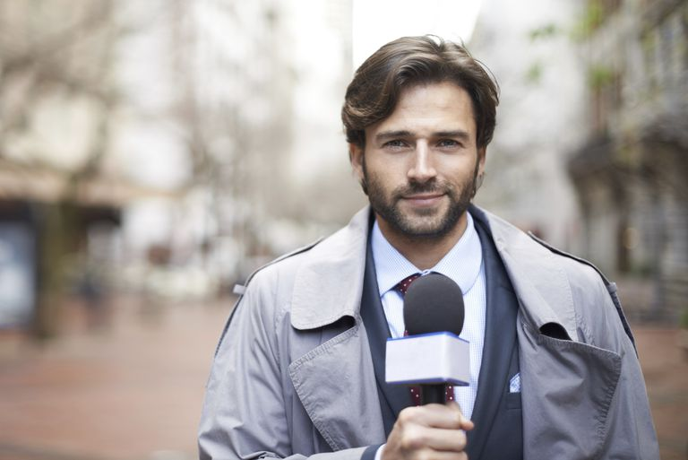 A photo of a TV news reporter at the scene of a story.